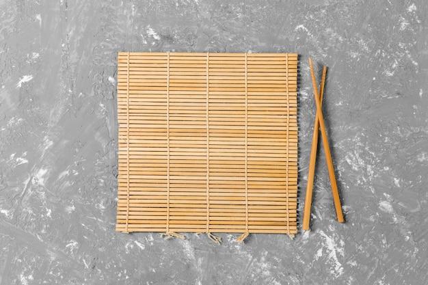 空の茶色の竹マットまたはセメントの背景に木製プレートと2つの寿司箸