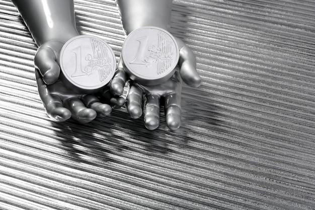 未来的なロボットの手の中の2つの銀ユーロ硬貨