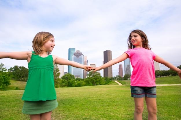 都市のスカイラインで手を握って遊ぶ2人の姉妹の女の子の友人