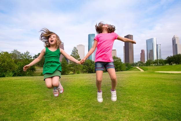 街のスカイラインで幸せな手を握ってジャンプ2人の女の子の友人