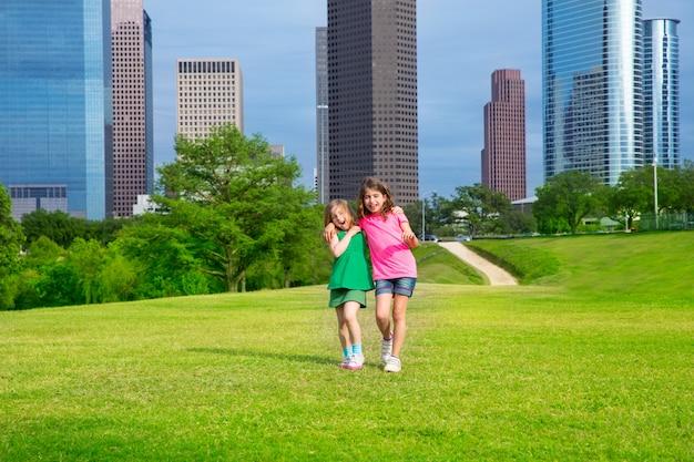 都市のスカイラインを歩く2人の姉妹の女の子友達