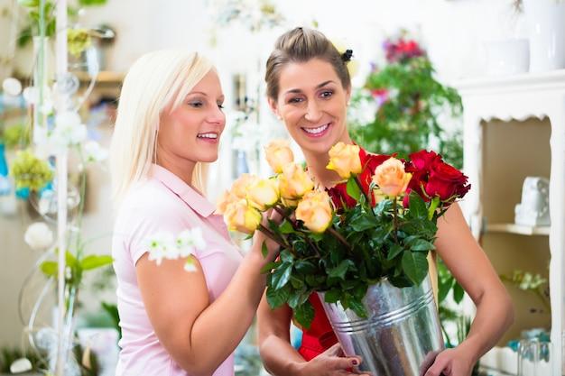 フラワーショップでバラの花束を見ている2人の女性