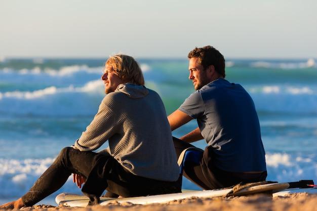 ビーチで話している2人のサーファー