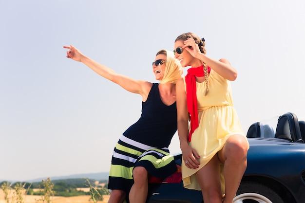 コンバーチブル車のボンネットの上に座っている2人の女性