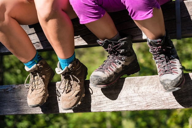 橋のレールの上に座ってハイキングブーツを持つ2人の子供
