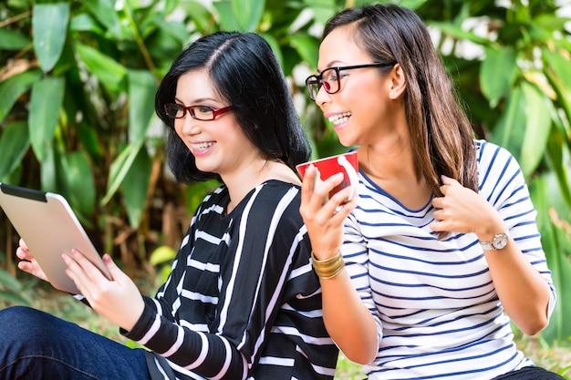タブレットコンピューターと2つのアジアのガールフレンド