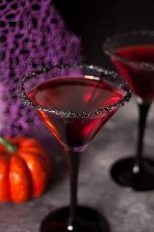 暗闇の中でハロウィーンパーティーのための赤いカクテルを2杯