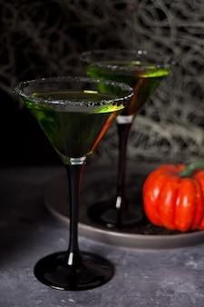 暗闇のハロウィーンパーティーのための緑のゾンビカクテルと2つのメガネ