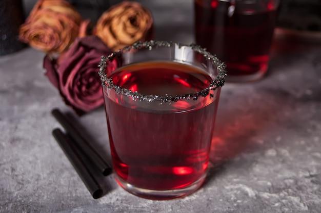 暗い背景にハロウィーンパーティーのための赤いカクテル、乾燥したバラと2つのメガネ