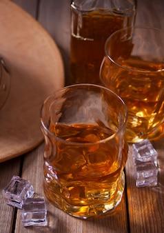 2 стекла вискиа и ковбойской шляпы на деревянном столе.