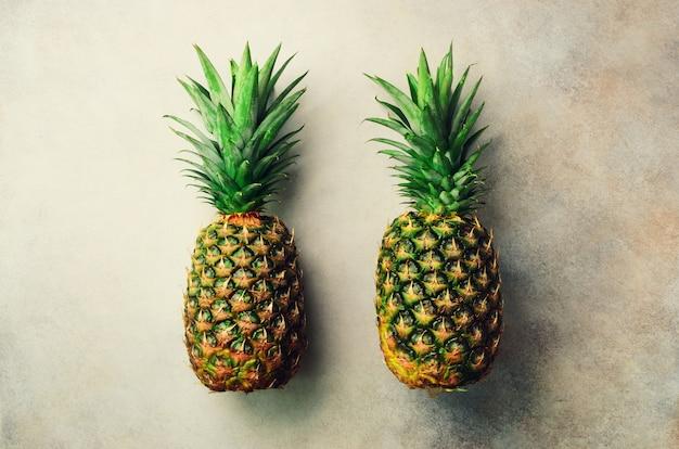 灰色の背景、上面図、コピー領域に2つのパイナップル。最小限のデザイン。ビーガンとベジタリアンのコンセプトです。パイナップルフルーツのマクロ