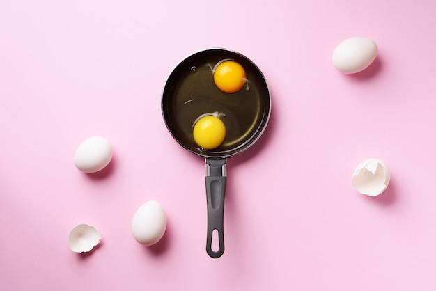 2つの卵、殻、ピンクの背景の上にパンの食品コンセプト