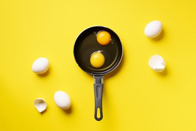 2つの卵、殻、黄色の背景上にパンの食品コンセプト