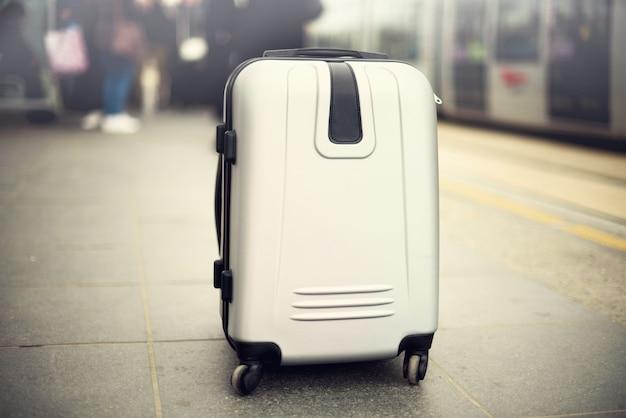 市内の電車に対して駅に立っている2つのスーツケース。
