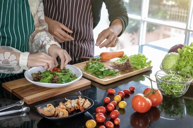 2人のシェフがキッチンでエビを炒めます。
