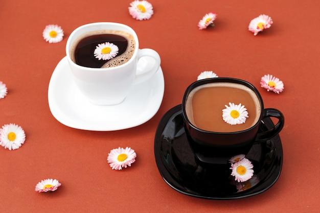 2 чашки кофе с маргаритками на коричневой предпосылке.