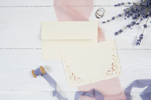 白い空白のカード、封筒、ピンクの布の上の2つの結婚指輪とリボン