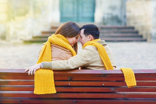 公園のベンチに座って、手で自分自身を保持している2人の恋人