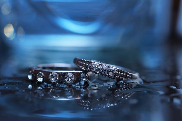 青い光の中で2つのリングのクローズアップを結婚式