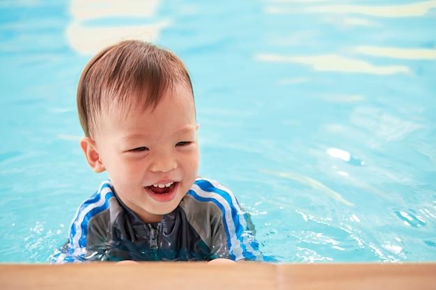スイミングプールの端にあるアジアの2歳の幼児男の子、小さな子供は屋内スイミングプールで水泳レッスン