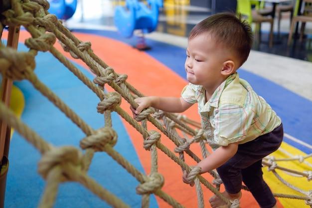 かわいい小さなアジア2歳幼児男の子子供楽しんで屋内の遊び場、物理的、手と目の調整、感覚、運動能力開発コンセプトでジャングルジムに登ろうとして