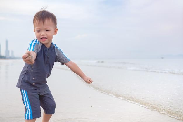ぬれた砂で覆われた汚れた手でビーチでかわいい小さなアジア2歳幼児男の子子供。家族旅行、夏のビーチでの休暇中の水の野外活動、砂のコンセプトでの感覚的な遊び