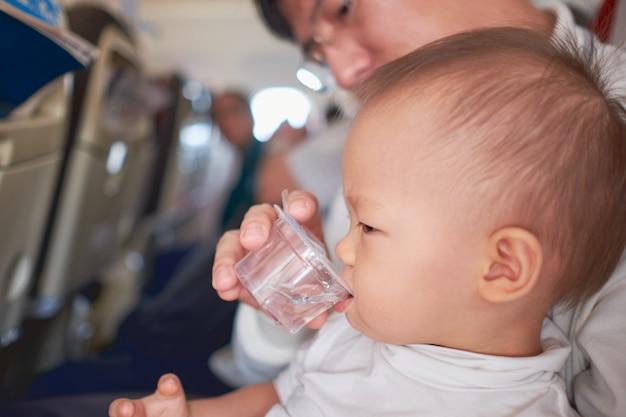 飛行機で飛行中にボトルから耳の飲料水が痛むのに苦しんでいるアジアの2歳の幼児男の子。飛行機の中で耳痛を感じる小さな子供