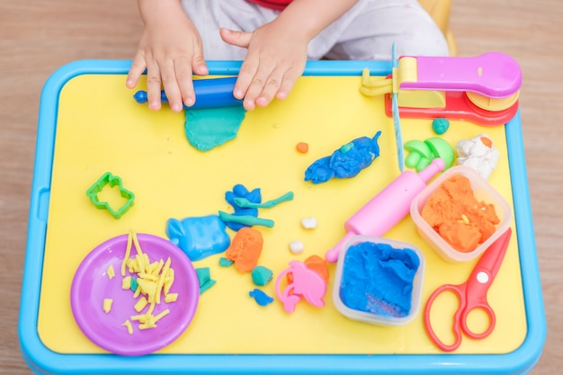Взгляд сверху маленького азиатского 2-летнего ребенка мальчика малыша, весело проводящего время, играя красочную лепку из глины / пьесы, готовя игрушки в игровой школе, развивающие игрушки творческая игра для концепции малышей