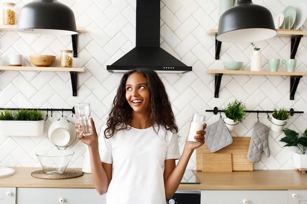 若いアフロ女性は水と牛乳で2つのメガネを保持します