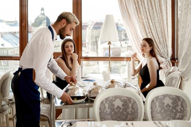ウェイターはレストランで2人の魅力的な女性に温かい料理を提供しています