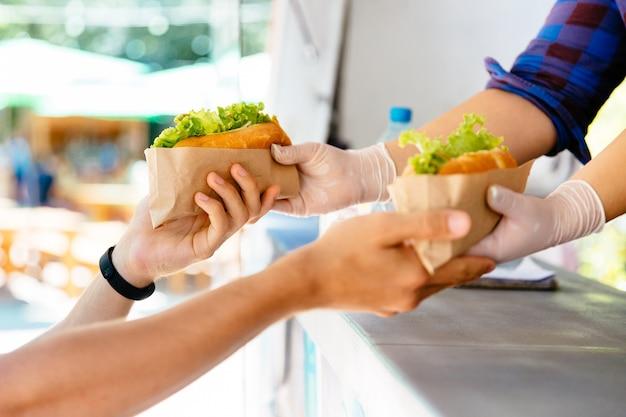 屋外で2つのホットドッグをキオスクで購入している男性。屋台の食べ物。クローズアップビュー。