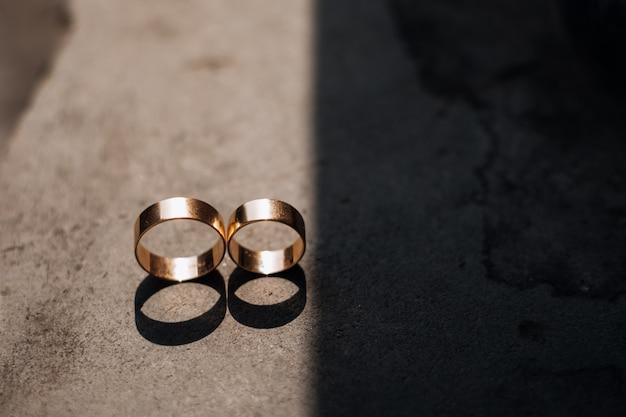 2つの黄金の結婚指輪が光線の中に横たわっています