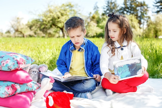 2人の子供が公園で本を読んでいます。教育の概念