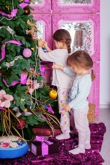 パジャマ姿の2人の妹がクリスマスツリーを飾りました。