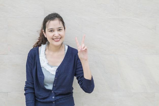 クローズアップアジアの女性は大理石の石の壁に笑顔で2本の指の動きを保持します。