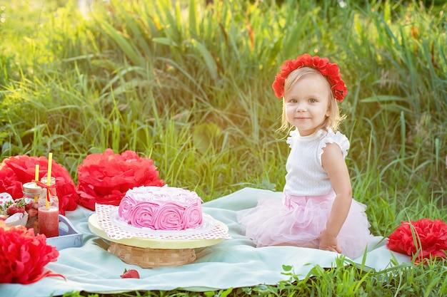 お祝いデコレーションのそばに座って、彼女の誕生日ケーキを食べる2歳の女の子。ケーキスマッシュ。