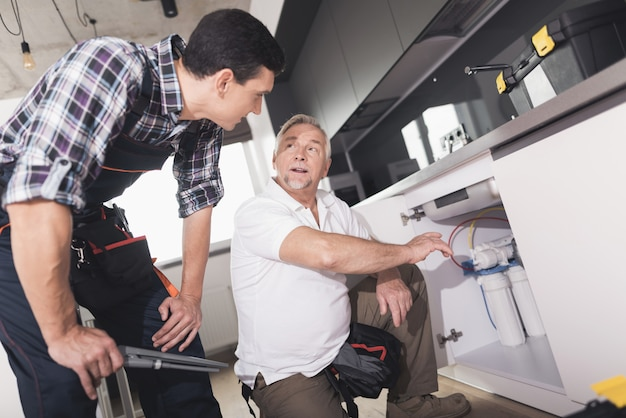 2人の配管工が台所の流しの修理を準備しました。