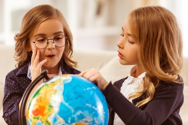 暗いジャケットを着た2人の美しい女の子が地球を考えています。