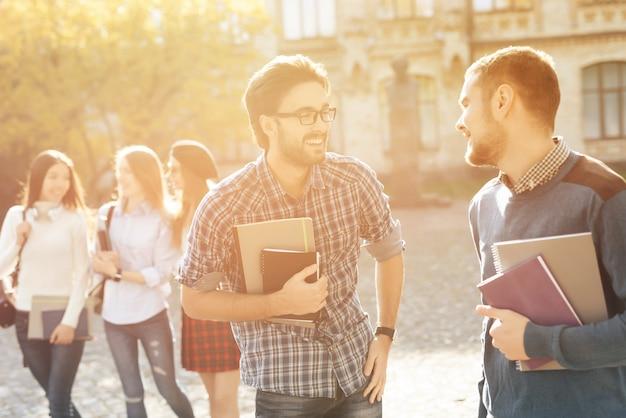 2人の学生が大学の中庭でコミュニケーションをとります。