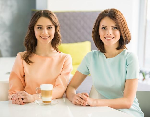 都市のカフェに座っている2人の若い美しい笑顔の女の子。