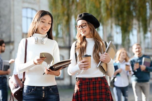 2人の女の子が一緒に大学の中庭で通信します