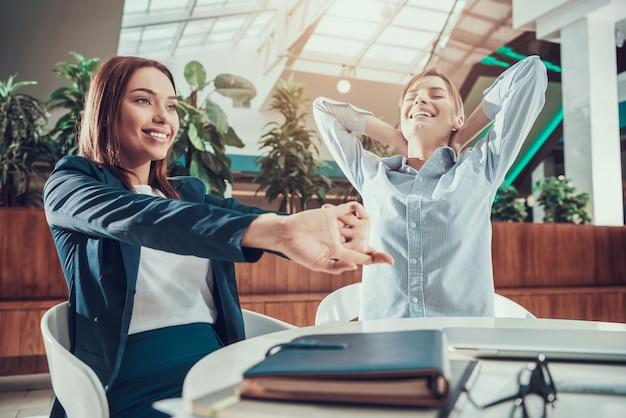 オフィスの机でストレッチを行使する2人の女性。