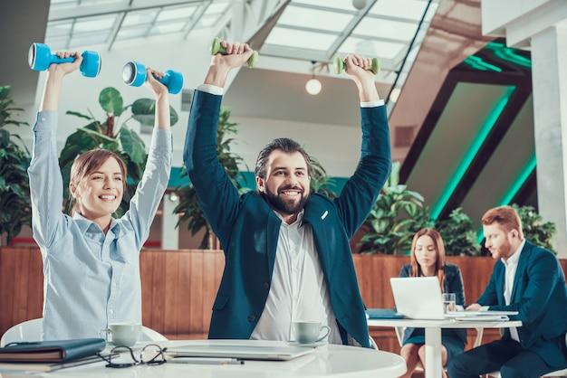 2 работника работая с гантелями на столе в офисе.