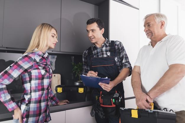女性は台所の流しを修理するために2つの配管工と呼ばれました