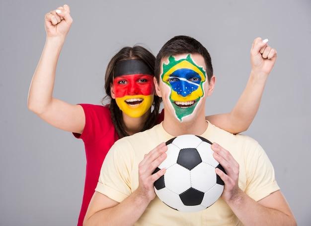 彼らの顔の旗を持つ2人の若いファンはボールを持っています。