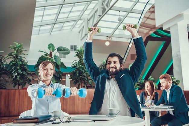 2人の労働者がオフィスでダンベル運動します。