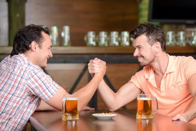 ビールを飲みながらパブで楽しんでいる2人の友人
