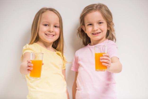 灰色のジュースを保持している2つのかわいい女の子