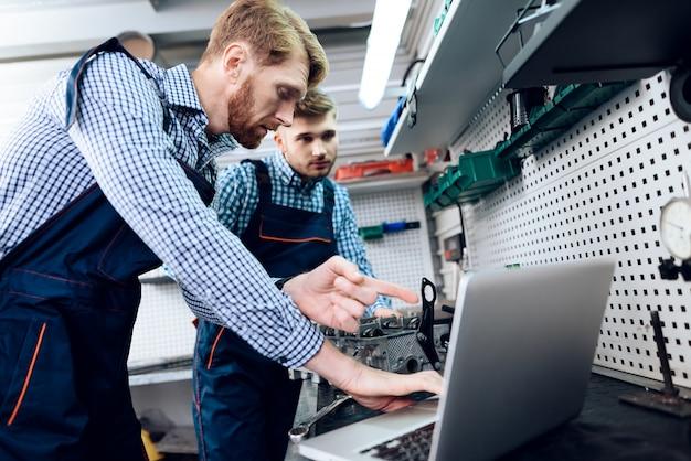 2つの自動車整備士がガレージで一緒に働いています。
