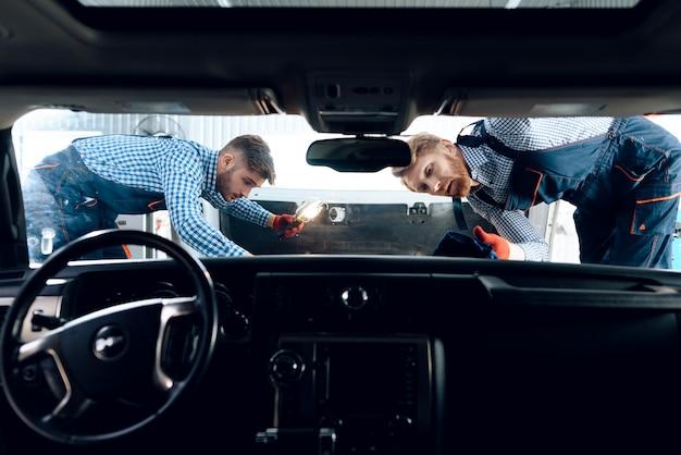 2つの自動車整備士がボンネットの下を見ています。